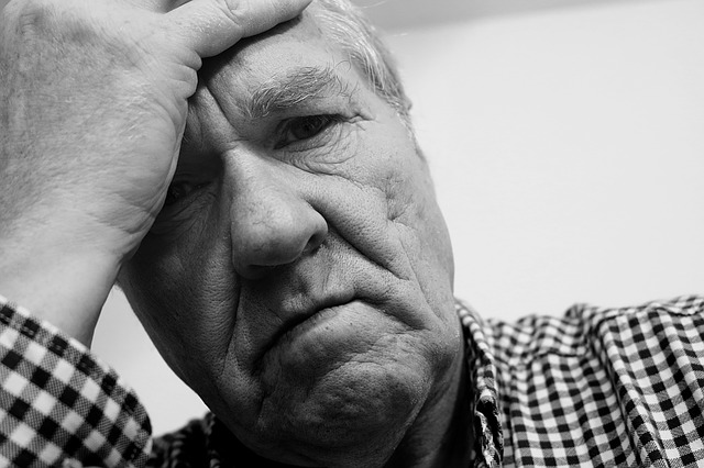 Black and white picture of old man holding his head